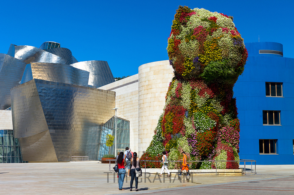 Tourists view Puppy flower feature floral art by Jeff Koons at Guggenheim Museum  in Bilbao, Basque Country, Spain