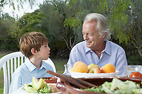 Grandfather and grandson (5-6) at garden table