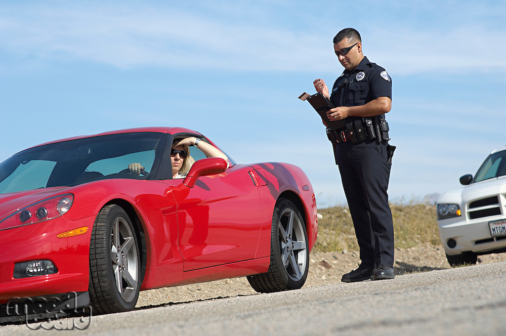 Traffic cop standing by sports car