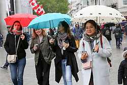 © Licensed to London News Pictures. 04/05/2019. London, UK. Tourists shelter under umbrellas in Trafalgar Square as it starts rain. Photo credit: Dinendra Haria/LNP