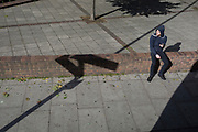 Aerial view of a youth using a mobile phone on next a diagonal pavement line, 21st September 2018, in London England