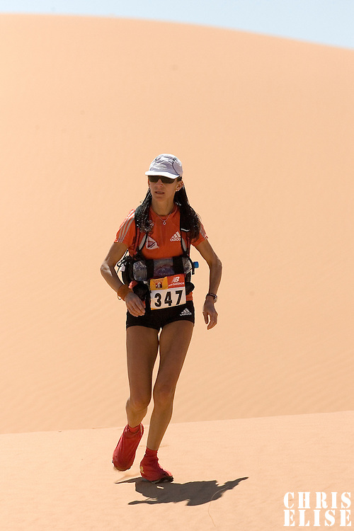 30 March 2007: #347 Laurence Fricotteaux of France runs in erg Znaigui en route to check point 3 during fifth stage of the 22nd Marathon des Sables between west of Kfiroun and erg Chebbi (26.22 miles). The Marathon des Sables is a 6 days and 151 miles endurance race with food self sufficiency across the Sahara Desert in Morocco. Each participant must carry his, or her, own backpack containing food, sleeping gear and other material.
