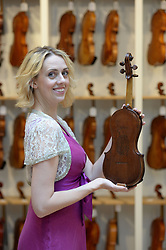 Musician Kerenza Peacock holds a violin made in the 1950s from one of Winston ChurchillÕs cigar boxes, in the London showroom of Ingles & Hayday, and which will be auctioned in their sale on 25 October at Sotheby's.
