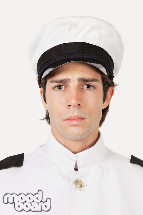 Portrait of young sad navy officer against gray background
