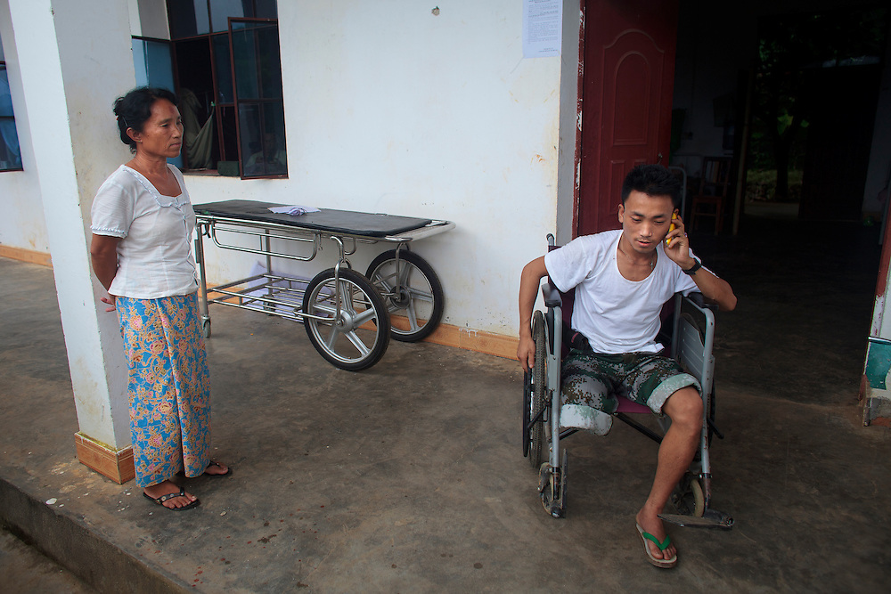 Kachin's militia member Lalaw Ze Dai, from Waimaw village, 25, talk on the phone while his mother, Lalaw Hkawn, watches him in the General Military Hospital in Laiza village close to the China border, Myanmar on July 19, 2012.  He was injured by landmine in June, 26, 2012 loosing part of his right leg on top of knee.