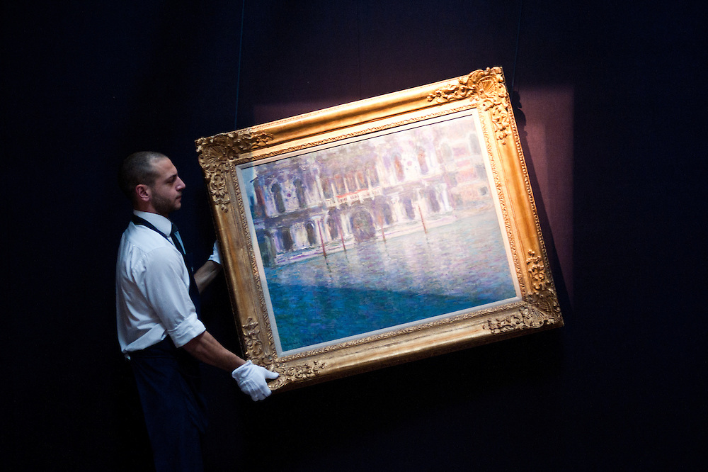 London,UK - 7 June 2013: A Sotheby's employee named Pietro holds 'Le Palais Contarini, 1908' by Claude Monet (Est. £15-20m) during the preview of this summer auction at Sotheby's estimated at £100 million.