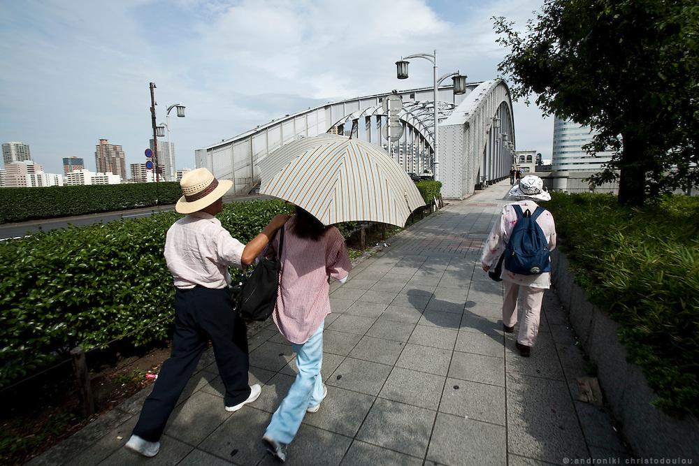 Couple walking towards a bridge over Sumida river