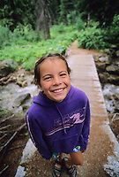 A girl, 10, smiles at the camera while hiking in Kokanee Provincial park, near Nelson, BC