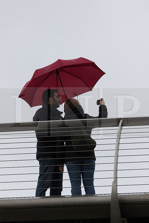 © Licensed to London News Pictures. 29/05/2015. London, UK. A couple with an umbrella try to take a photograph from the Millennium bridge during wet and overcast weather in London. Today is the first day of British Summer Time (BST). Photo credit : Vickie Flores/LNP