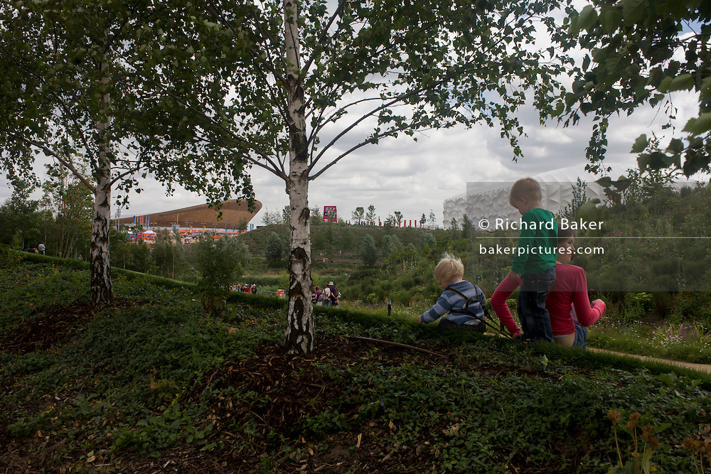 Young spectators admire the English garden flowers with the main Olympic stadium and basketball arena in the background during the London 2012 Olympics. London's Olympic Park, at just under a square mile, is the largest new park in the city for more than 100 years. The planting of 4,000 trees, 300,000 wetland plants and more than 150,000 perennial plants plus  nectar-rich wildflower make for a colourful setting for the Games. This land was transformed to become a 2.5 Sq Km sporting complex, once industrial businesses and now the venue of eight venues including the main arena, Aquatics Centre and Velodrome plus the athletes' Olympic Village. After the Olympics, the park is to be known as Queen Elizabeth Olympic Park.