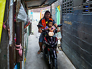 "22 MARCH 2018 - BANGKOK, THAILAND: A motorcycle taxi takes a fare past a demolished home along Khlong Lat Phrao. Bangkok officials are evicting about 1,000 families who have set up homes along Khlong  Lat Phrao in Bangkok, the city says they are ""encroaching"" on the khlong. Although some of the families have been living along the khlong (Thai for ""canal"") for generations, they don't have title to the property, and the city considers them squatters. The city says the residents are being evicted so the city can build new embankments to control flooding. Most of the residents have agreed to leave, but negotiations over compensation are continuing for residents who can't afford to move.      PHOTO BY JACK KURTZ"