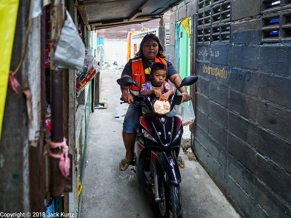 """22 MARCH 2018 - BANGKOK, THAILAND: A motorcycle taxi takes a fare past a demolished home along Khlong Lat Phrao. Bangkok officials are evicting about 1,000 families who have set up homes along Khlong  Lat Phrao in Bangkok, the city says they are """"encroaching"""" on the khlong. Although some of the families have been living along the khlong (Thai for """"canal"""") for generations, they don't have title to the property, and the city considers them squatters. The city says the residents are being evicted so the city can build new embankments to control flooding. Most of the residents have agreed to leave, but negotiations over compensation are continuing for residents who can't afford to move.      PHOTO BY JACK KURTZ"""
