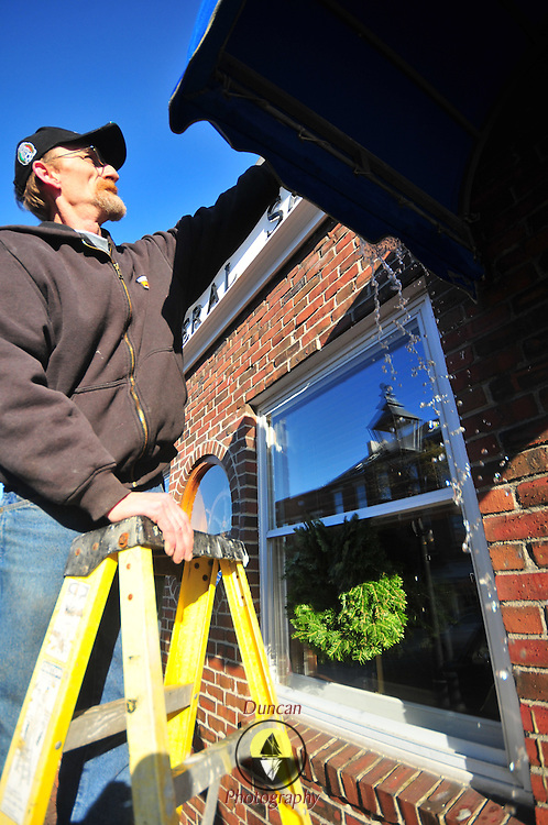 12/11/10  - BATH, Maine. -- Mike Carlton, maintenance man for First Federal Bank in Bath, washes down the ATM canopy on Saturday afternoon. Photo by Roger S. Duncan.