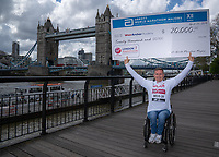David Weir accepts a cheque on behalf of the Weir Archer Academy from Abbott World Marathon Majors for £20,000 to mark his 20th consecutive London Marathon at a photocall for Elite Wheelchair athletes at the Guoman Tower Hotel. The Virgin Money London Marathon, 25 April 2018.<br />