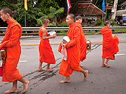 "28 JUNE 2011 - CHIANG MAI, THAILAND:  Buddhist monks on their morning alms rounds in Chiang Mai, Thailand. The monks go out every morning and solicit food from the people in the neighborhood. For the people who provide food and other supplies, it's a way to ""make merit"" for the afterlife.  PHOTO BY JACK KURTZ"