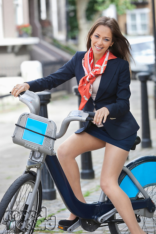 Portrait of happy young businesswoman with bicycle