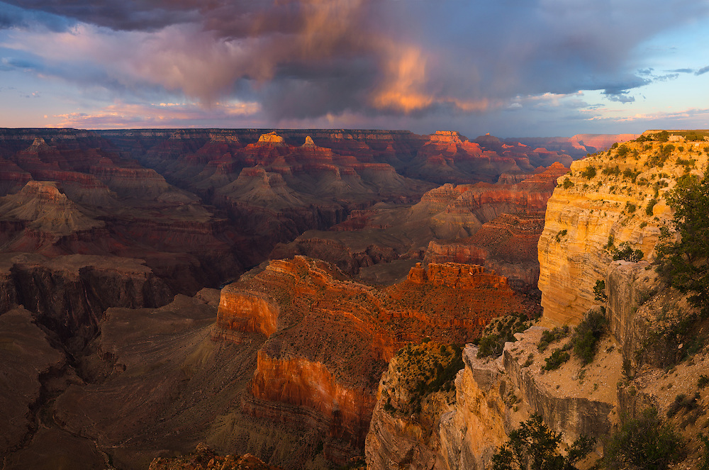 Sunset from the South Rim of Grand Canyon National Park near Hopi Point. In the distance to the right is a single person standing on the rim at Powell Point, showing the massive scale of the Grand Canyon.