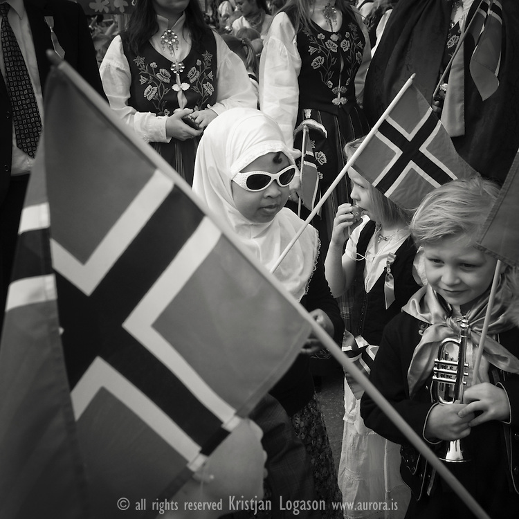 Young girls, one of them wearing sunglasses and turk, the other holding a trompet,  preparing for a walk in the parade on Norways national day 17th of may in the city of Mo i Rana North Norway