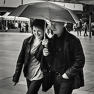 Man and a woman walking sheltered by an umbrella in the rain at torgalmenningen square in central Bergen, Hordaland Norway