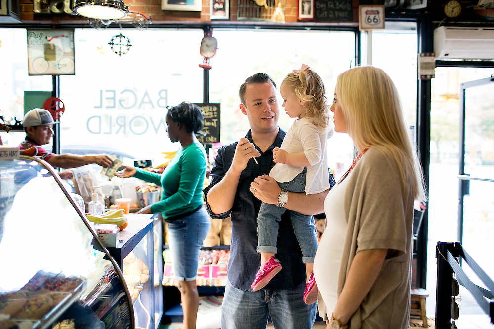 NEW YORK, NY - OCTOBER 19, 2016:  Brendan Burke, the new Islanders play-by-play announcer, stops at a bagel shop with his wife Mary and two-year-old daughter Quinn before heading to a park in the Park Slope neighborhood of Brooklyn, New York. CREDIT: Sam Hodgson for The New York Times.