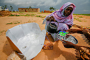 A woman pours tea in a refugee camp in Touloum in Tchad, close to the sudanese border. The tea is boiled in a solar cooker, manufactured by women in the camp.  More than 23.000 refugees from Darfur, mainly women and children, live in the camp. The benefits of solar cookers are huge: Traditionally women do the hard job of gathering wood for fire. In a barren, conflict ridden area like the Darfur border, the women walk long distances in search of the wood, and are often assaulted and raped. The solar cookers alleviate both the hard work and the dangers facing these women.  <br /> Countries in the SAHEL area are not the big emitters of greenhouse gases. Tchad emitted about 0.5 metric tons in 2013, while the US and China emitted 5233 and 9977 metric tons respectively.<br /> In the draft being presented at the COP21 in Paris, poorer countries demand financial aid to help transition to renewable energy, as well as help to cope with climate change. Countries most at risk also demand a tougher target of 1.5 degrees &ndash; a cap supported by climate change scientists. As Penn State climate scientist Petra Tschakert put it, the 2 degree cap is &ldquo;utterly inadequate&rdquo;.