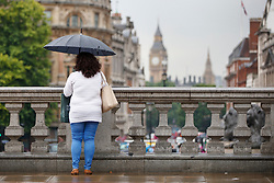 © Licensed to London News Pictures. 27/06/2017. London, UK. Tourists take shelter from the rain under umbrellas in Trafalgar Square, London on Tuesday, 27 June 2017. Photo credit: Tolga Akmen/LNP