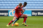 Coventry City midfielder Gael Bigirimana holds up Oldham Athletic midfielder Aaron Phillips during the Sky Bet League 1 match between Coventry City and Oldham Athletic at the Ricoh Arena, Coventry, England on 19 December 2015. Photo by Alan Franklin.