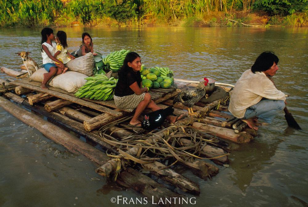 Machiguenga indian family rafting to market, Tambopata River, Peru
