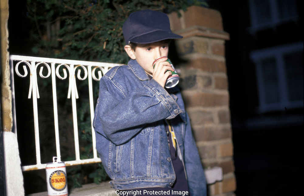 Young teenage boy drinking in street.