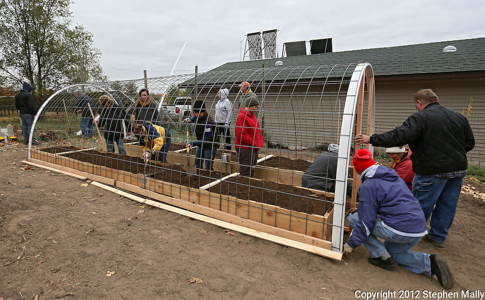 Workshop attendees work out the outside frame and inside planters of the hoop house during a Hoop House and Root Zone Heating Workshop at Prairiewoods in Hiawatha on Saturday October 6, 2012.