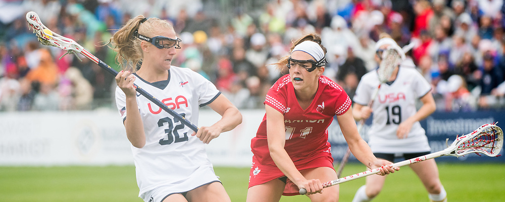 USA's Allyson Carey(32) and Canada's Erica Evans(11) at the 2017 FIL Rathbones Women's Lacrosse World Cup at Surrey Sports Park, Guilford, Surrey, UK, 15th July 2017