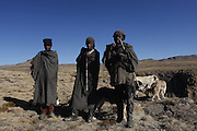 Tribesman from the kingdom of Lesotho and their dogs stand at the top of the well known Amphitheatre in the northern DrakensbergThe Drakensberg mountains of South Africa or uKhahlamba is a 200-kilometre-long mountainous wonderland and world heritage site. The largest proportion of the Drakensberg area falls in the province of KwaZulu-Natal.