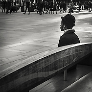Man with hat sitting on a stone benche at torgalmenningen in central Bergen Norway listening to music and watching pwople pass by