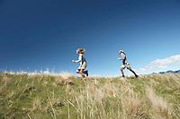 Man and woman running through field
