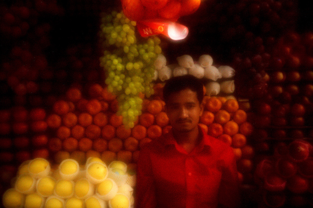 Dream of Dhaka..An anonymous fruit salesman in the city center...Dhaka, the fastest growing megacity in the world, is flooded by between 4 to 500.000 new people every year. A growth double its entire population of the 1947 census when India was partitioned. The people currently residing in Dhaka is sharing each square kilometer with an average of approximately 20.000 other people. According to local estimates more than 15.000.000 people inhabits the giant metropolis, dubbed by the World Bank as the fastest growing megacity in the world. The exponential growth is progressing towards an expected 25 million people by 2025. The Dreamers of Dhaka more often than not end up as squatters large slums under conditions less than favorable with the unfortunate third; the city-dwellers destitute of rights and land. Solitude, silence and personal space are luxury commodities for the few who can afford to reflect and act upon it in this ever growing society...Photo by: Eivind H. Natvig/MOMENT
