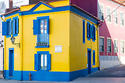Brightly coloured pink, blue and yellow facades, balconies, shutters in Cais dos Botiroes by the marina at Aveiro, Portugal