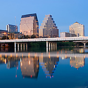Buildings of downtown Austin Texas and the Congress Ave Bridge reflected on still water of Town Lake at dusk. The shot is taken from the southern bank of the lake facing east.
