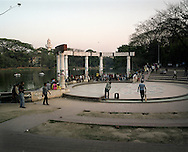 Young people play cricket in Dhanmondi Lake Park in Dhaka.