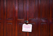 "A sign hanging from the closed door of a shop says ""Sorry we are closed for prayers"". Location is Malacca, Malaysia, during the month of Ramadan"