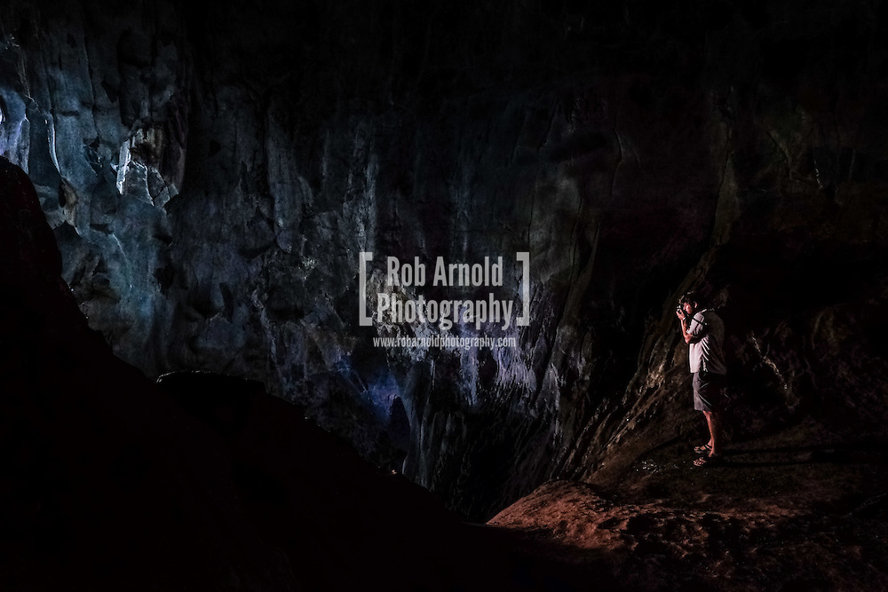 A photographer takes a photograph within Pha Tok Cave, near Nong Khiaw in northern Laos