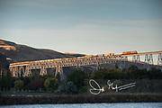 A Union Pacific railroad train crosses the Joso High Bridge at sunrise.