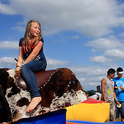 Kayla Bileth, 8, rides a mechanical bull during the Town of Leland's Founder's Day Saturday September 14, 2013. (Jason A. Frizzelle)