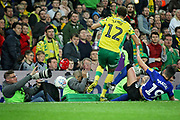 Norwich City defender Jamal Lewis (12)  and Sheffield Wednesday forward Marco Matias (19) disappear into the photographers pit during the EFL Sky Bet Championship match between Norwich City and Sheffield Wednesday at Carrow Road, Norwich, England on 19 April 2019.
