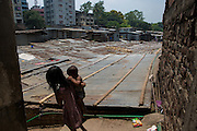 A girl carries a baby down some stairs to a slum area of Dhaka, Bangladesh.