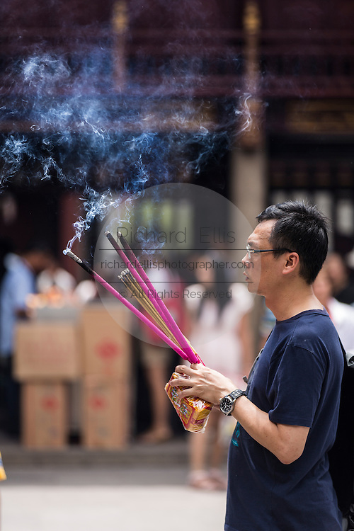 A man prays at Chenghuang Miao or City God Temple in Yu Yuan Gardens bazaar Shanghai, China