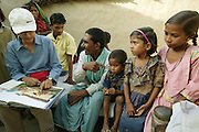 IND.MWdrv04.164.x..Peter Menzel and Faith D'Aluisio's translator and friend, Neha Diddee, compares the family in the Material World book 1994 Yadav family photograph to family members now. Ahraura Village, Uttar Pradesh, India. Revisit with the family, 2004. The Yadavs were India's participants in Material World: A Global Family Portrait, 1994 (pages: 64-65), for which they took all of their possessions out of their house for a family-and-possessions-portrait..