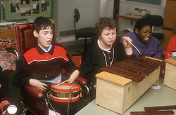 Group of young children with learning disabilities taking part in school music lesson,