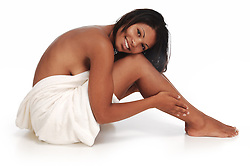 beautiful Aftrican-American woman with hand on leg with white towel on whtie background