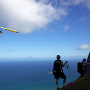A tandem hang glider flies above the hillside of Pedro Bonita high in the hills of Rio de Janeiro as a tandem para glider prepares to take off. Pilots of hang gliders and para gliders take tourists for tandem flights with breathtaking views of the city before landing on Sao Conrado beach. Rio de Janeiro,  Brazil. 9th September 2010. Photo Tim Clayton