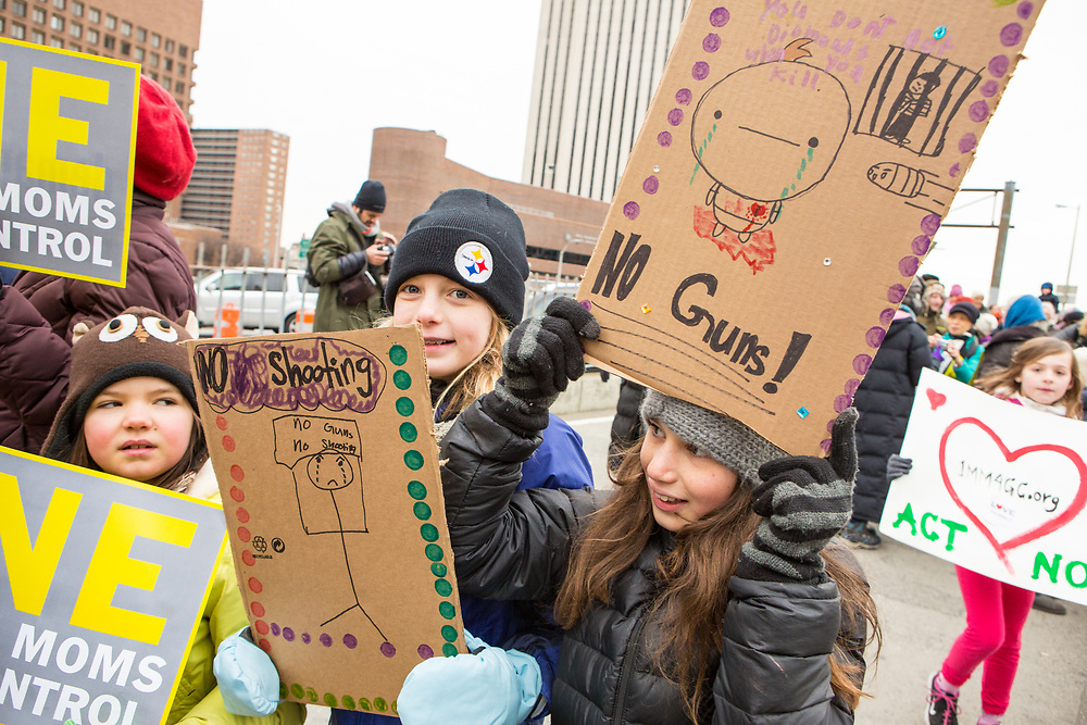 Children carry home made signs in favor of gun control.